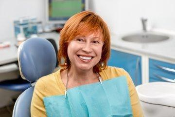 Woman smiling in dental chair after periodontal exam in boise