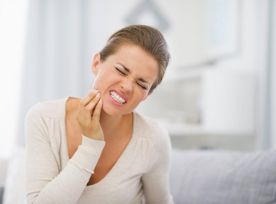 woman holding jaw from tooth pain during dental emergency