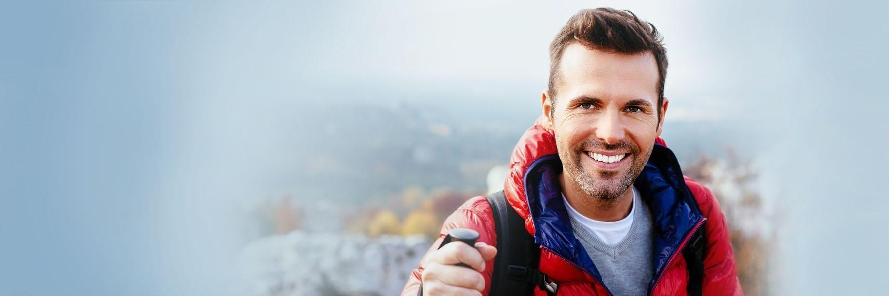 Man in red jacket smiling while hiking